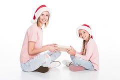 愉快的戴圣诞老人帽子,坐地板和拿着礼物盒的母亲和女儿, 图库摄影