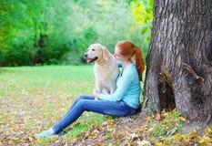 愉快的所有者妇女和金毛猎犬在公园尾随一起坐 免版税库存照片