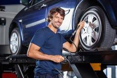 愉快的技工填装的空气到在车库的车胎里 图库摄影