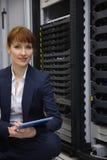 愉快的技术员坐在服务器塔旁边的地板使用片剂个人计算机 免版税库存图片
