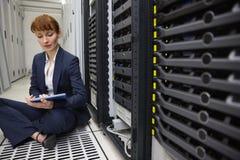 愉快的技术员坐在服务器塔旁边的地板使用片剂个人计算机 库存照片