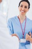 愉快的护士与医生握手 图库摄影