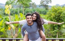 愉快的拉丁人运载妇女支持,在绿色热带雨林风景的年轻夫妇 免版税库存图片