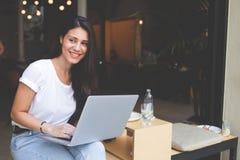 愉快的拉丁妇女坐与在现代边路咖啡店的开放膝上型计算机 图库摄影