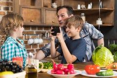 愉快的拍女儿的照片家庭在厨房里,父亲和儿子烹调在细胞巧妙的电话的食物 免版税图库摄影