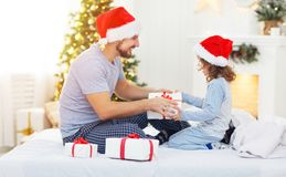 愉快的拥抱和给在克里斯的家庭父亲和孩子礼物 免版税库存照片