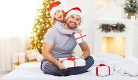愉快的拥抱和给在克里斯的家庭父亲和孩子礼物 免版税库存图片