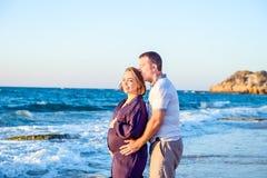 愉快的拥抱和观看向前对海的爱怀孕的夫妇画象在海滩的步行期间 由c放松 库存图片