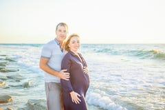 愉快的拥抱和观看对海的爱怀孕的夫妇画象在海滩的步行期间 由风平浪静放松  库存照片