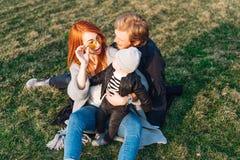 愉快的拥抱在公园的妈妈爸爸和儿子 免版税库存照片