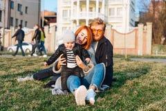 愉快的拥抱在公园的妈妈爸爸和儿子 图库摄影