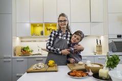 愉快的拥抱在厨房里的母亲和儿子 免版税库存图片