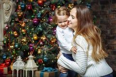 愉快的拥抱在圣诞树附近的家庭母亲和女儿 库存照片