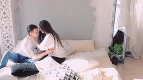 年轻愉快的拥抱在床上的家庭一起,女孩和人 亲吻丈夫的妻子 夫妇欧洲人出现 概念  股票录像