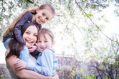 愉快的拥抱在春天的母亲和两个孩子 免版税库存图片