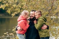愉快的拥抱在秋天的父亲和逗人喜爱的小孩 库存照片