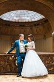 愉快的拥抱在老冰屑玻璃天花板前面的新郎和新娘在富有的木内部 免版税库存图片