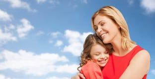 愉快的拥抱在蓝天的母亲和女儿 免版税图库摄影