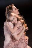 愉快的拥抱在黑色的母亲和女儿 免版税库存照片