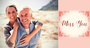 愉快的拥抱的夫妇的综合图象在看照相机的海滩的 库存图片
