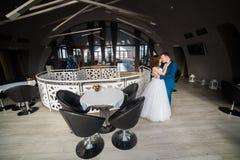 愉快的拥抱的新婚佳偶夫妇在时髦的餐馆花费时间 免版税图库摄影