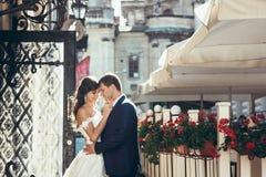愉快的拥抱的新婚佳偶的水平的结婚照晴朗的街道的 新娘抚摸面颊  库存照片