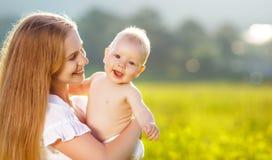 愉快的拥抱自然的家庭母亲和婴孩在夏天 免版税库存图片