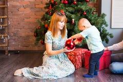 愉快的拿着中看不中用的物品的母亲和可爱的婴孩反对与圣诞树的国内欢乐背景 免版税图库摄影