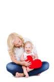 愉快的拿着红色心脏的母亲和她的孩子 免版税库存图片