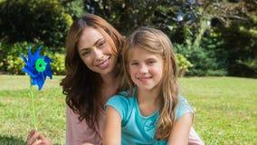 愉快的拿着轮转焰火的母亲和女儿 免版税库存照片