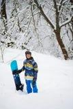 愉快的挡雪板在冬天森林里站立在降雪以后 库存照片