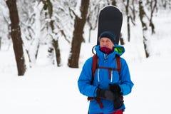 愉快的挡雪板在冬天森林里站立 免版税库存照片