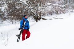 愉快的挡雪板在冬天森林,赞赏的冬天l里站立 免版税库存照片