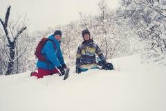 愉快的挡雪板在深雪坐在freeride以后 免版税库存图片