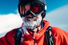 愉快的挡雪板在红色衣服站立 免版税库存图片