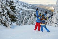愉快的挡雪板,有开放胳膊的,在山坡站立 库存图片