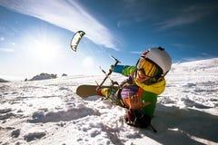 愉快的挡雪板说谎并且拿着snowkite 库存图片