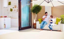 愉快的放松在伞阴影笼罩下的父亲和儿子在有露天场所厨房的屋顶露台 免版税库存图片