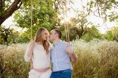 愉快的放松在自然,愉快的家庭,怀孕的夫妇未来父母 免版税库存图片