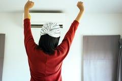 愉快的新妇女在空调器的前面开关的手和身分 免版税库存照片