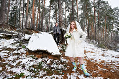 愉快的新娘和新郎在冬天森林里 免版税图库摄影