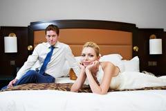 愉快的新娘和新郎在卧室 免版税库存照片