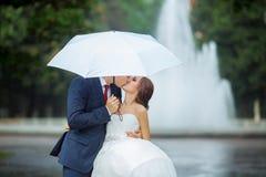 愉快的新娘和新郎在婚礼步行白色伞 免版税库存图片