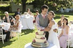 愉快的新娘和新郎在婚宴喜饼前面在庭院里 免版税图库摄影