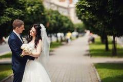 愉快的新娘和新郎在晴朗的胡同在婚礼走 免版税库存照片