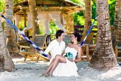 愉快的新娘和新郎获得乐趣在一热带beac的一个吊床 免版税库存照片