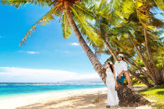 愉快的新娘和新郎获得在一个热带海滩的乐趣在棕榈下 库存照片