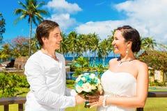 愉快的新娘和新郎获得在一个热带海滩的乐趣在p下 免版税图库摄影