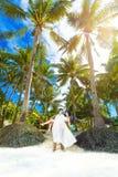 愉快的新娘和新郎获得在一个热带海滩的乐趣在p下 库存照片
