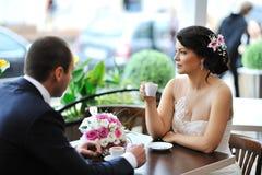 愉快的新娘和新郎饮用的咖啡在一个室外咖啡馆 库存照片